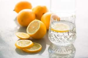 A glass of lemon water with sliced lemons