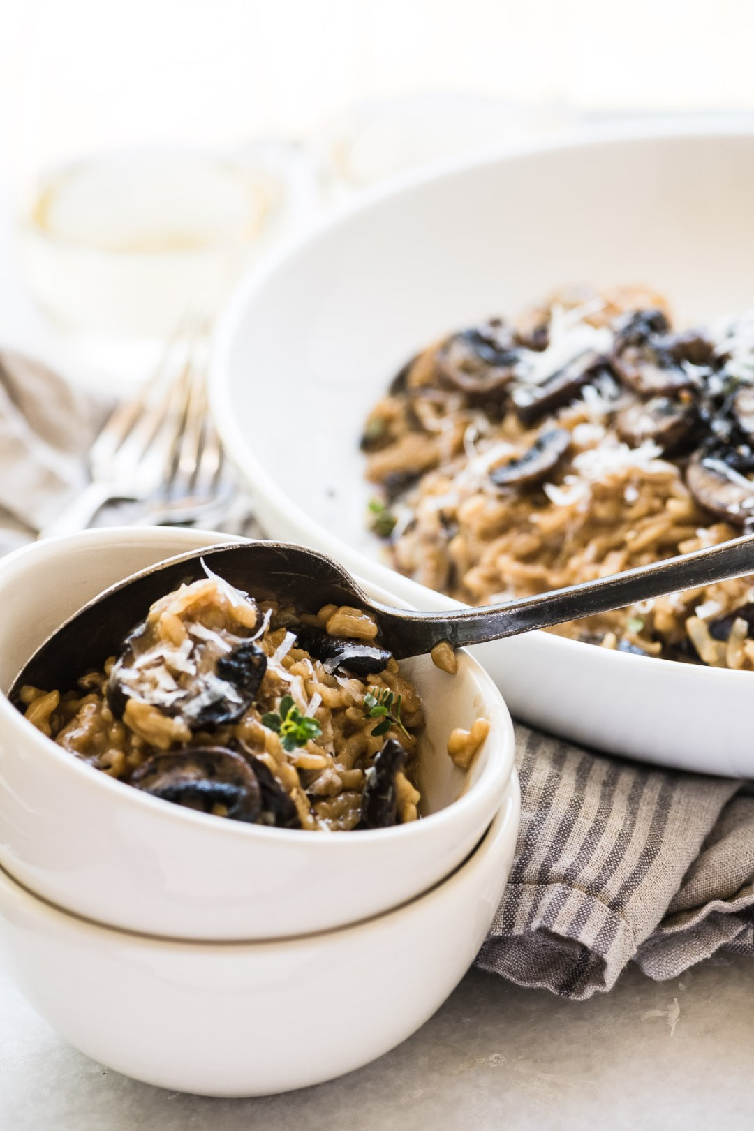 Instant Pot Wild Mushroom Risotto being spooned into a small white bowl