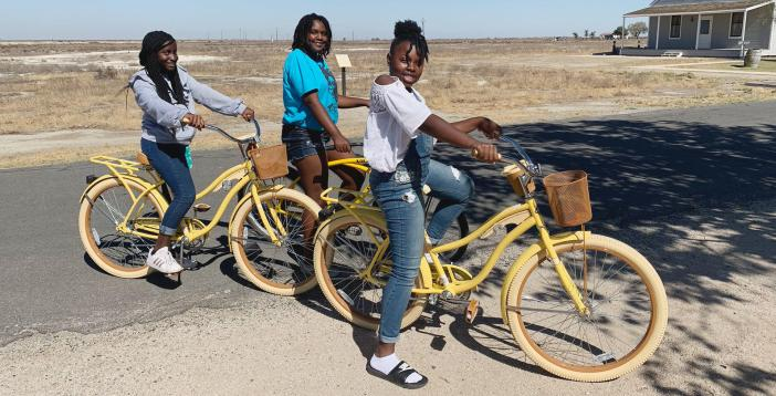 Three girls out for a bike ride via The Village Method programming