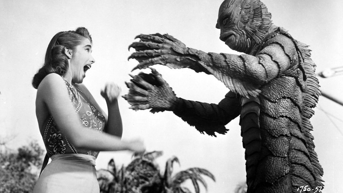 The creature tries to grab Julie Adams