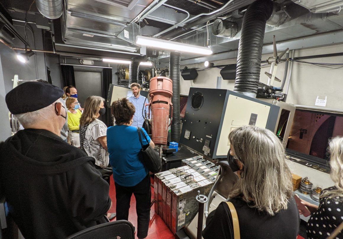 a crowd of people inside a film projection booth
