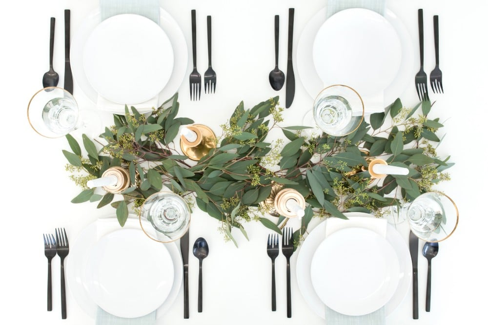 Overhead view of a table set for Thanksgiving with white plates, black cutlery and a grennery centerpiece.