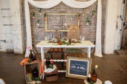 White Sweetheart Table, Crates, Brown Bottles, Geo Terrarium, Signs, Lettering, Chairs, Drapery by The Event Styling Company