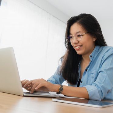 Young beautiful Asian woman working with laptop,smartphone and tablet in home office background.Concept of female freelancer using gadget mobile technology.