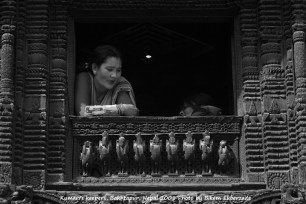 Bakhtapur, Nepal -- Kumari's keepers (most likely her family) look out the window, where the goddess of Nepal also known as Kumari, often a teenage girl child, is selected to reside in Durbar Square, Kathmandu, Nepal. Photo by Bikem Ekberzade
