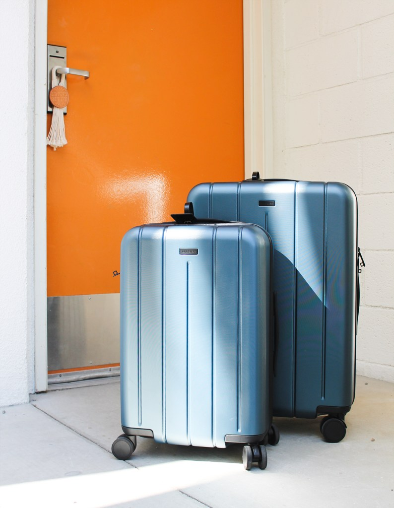 CHESTER luggage small and medium, navy colored, in front of a bright orange door.