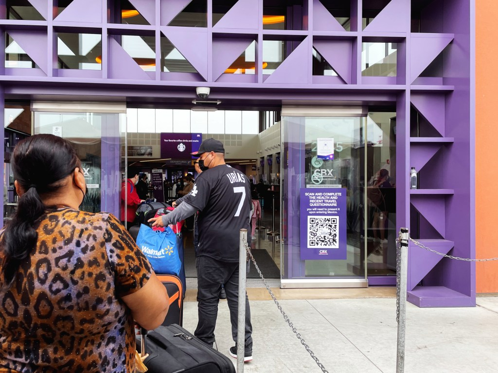 Exterior of CBX 2021, purple geometric doorway with QR code link to the health questionnaire