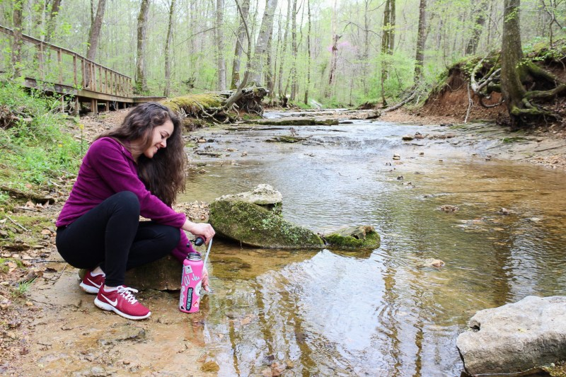 woman getting clean water from a creek while hiking by using the msr gear trailshot water filter