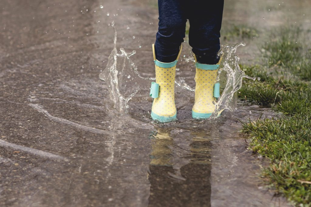 child rainboots jumpin in puddle of rain water
