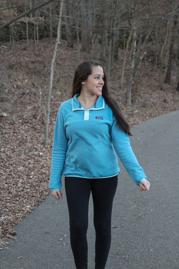 woman wearing a blue pullover fleece jacket and black leggings while hiking outdoors.
