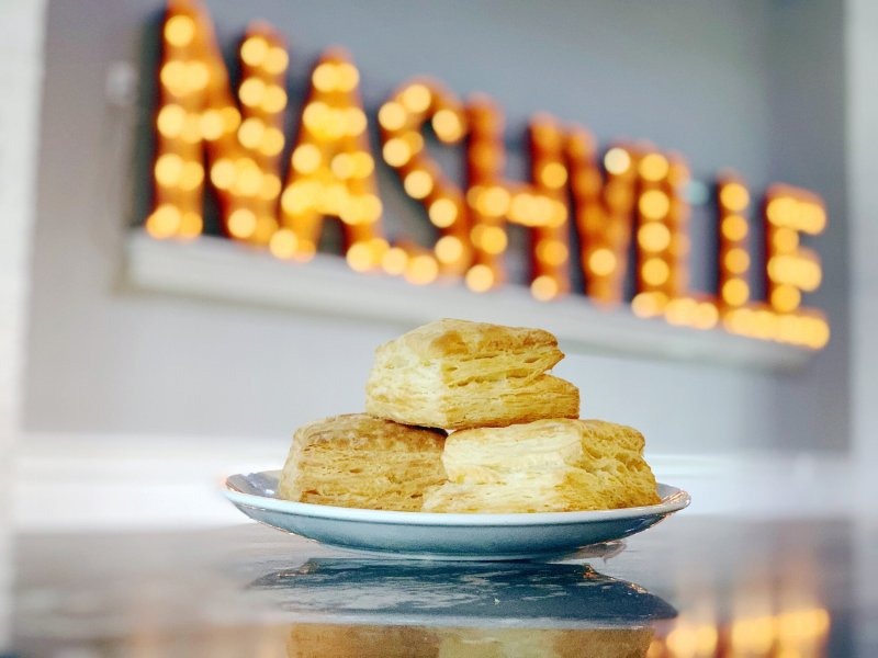 Ultimate Travel Guide To The Gulch in Nashville, Tennessee. Delicious plate of biscuits from Biscuit Love with a sign of Nashville in the background.
