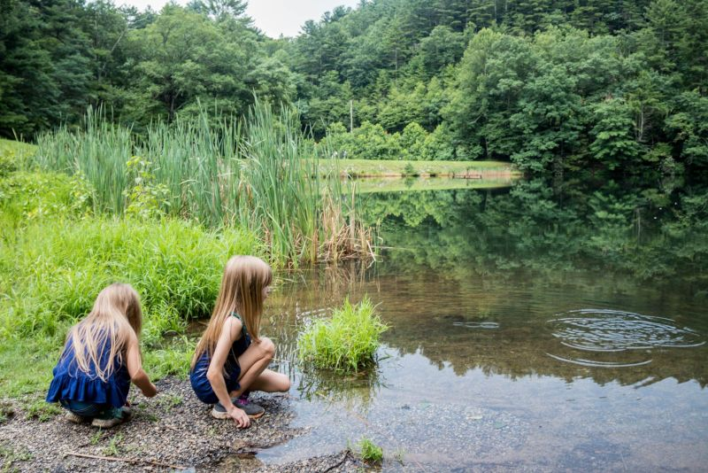 Two girls playing by the lake during their camping trip. Camping Etiquette -  Camping with Kids