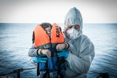 A young boy, traumatized and whimpering with fear is lifted to safety aboard Italian rescue vessle, Spica