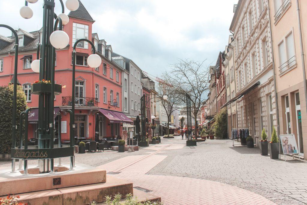 Een klassieke winkelstraat met tegels en lantaarnpalen met bollen in Luxemburg.