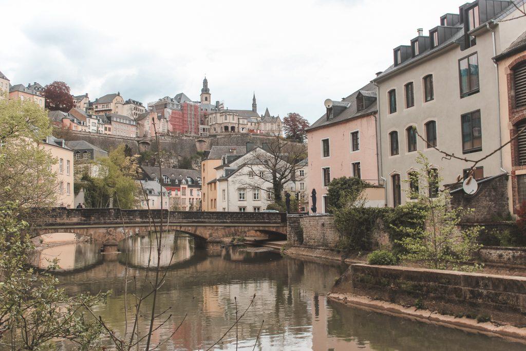 Oude stenen brug over water omringd door beige kleurige huizen.