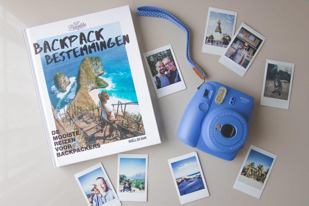 Het boek Backpack bestemmingen omringd door polaroidfoto's.