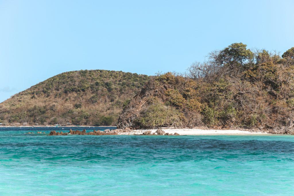 Azuurblauw water Filipijnen met op achtergrond heuvelachtig eiland.