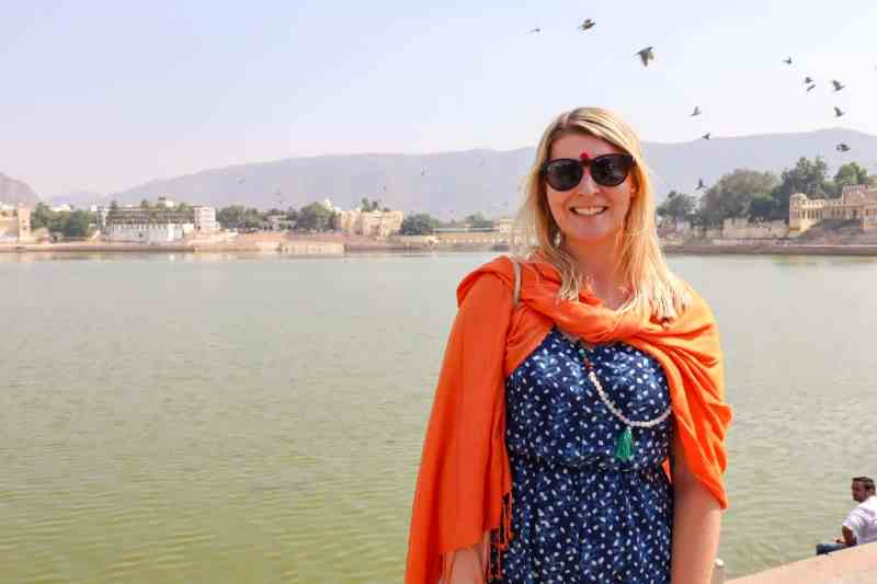 ellie quinn with orange shawl at pushkar lake