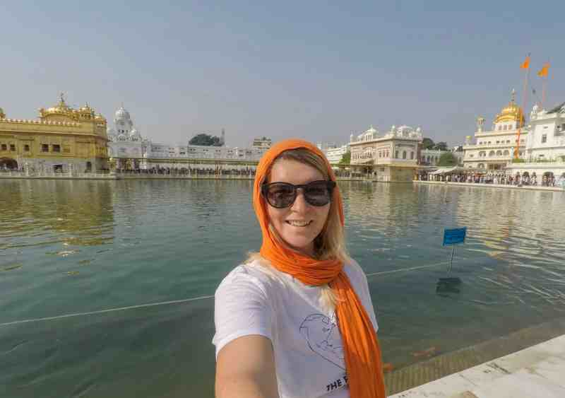 ellie quinn in orange head scarf in the golden temple in Amritsar