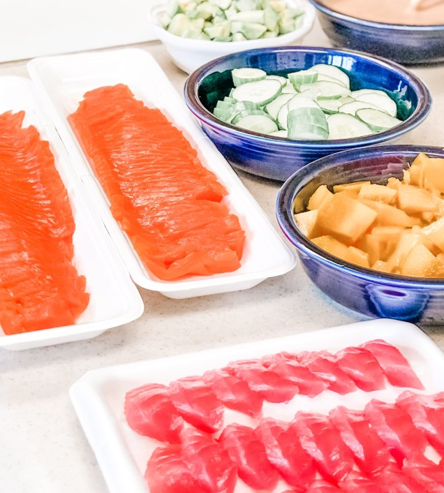 Sushi ingredients including sliced salmon, sliced tuna, chopped mango, sliced cucumbers and chopped avocado