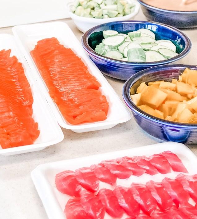 Sushi ingredients including sliced salmon, sliced tuna, chopped mango, sliced cucumbers and chopped avocado