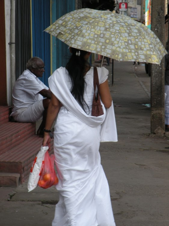 Her white sari doesn't necessarily indicate she is in mourning - she could be returning from the temple..