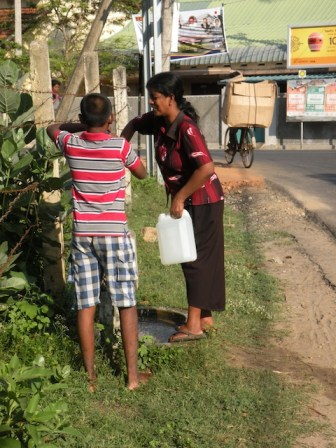 Collecting water from taps in the street, four years after the war had ended.