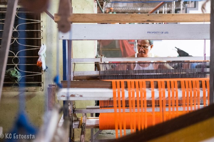 A man weaves an abel blanket using a hand loom