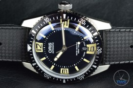 OrisDivers Sixty-Five laying on its side on a black leather surface [01 733 7707 4064-07 4 20 18]