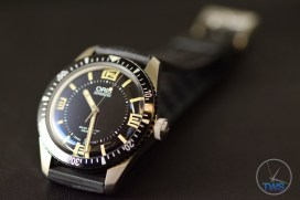 OrisDivers Sixty-Five Laying back on its strap at an angle on black leather with the clasp going out of focus in the background [01 733 7707 4064-07 4 20 18]