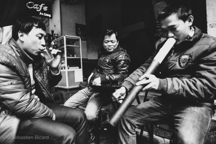 Young men having a conversation over an afternoon tea and water pipe in the French Quarter of Hanoi. Vietnam, February 2014.