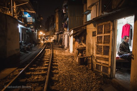 A man spends his evening at home, just a few feet from the passing trains on the track through central Hanoi. Vietnam, February 2014.