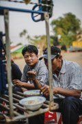 Tuk-tuk drivers grab some noodles for a quick breakfast on the back of their rig. Tha Khaek, Laos, April 2014.