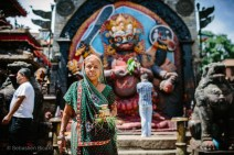 A woman brings her offering to a colorful Hindu temple in Kathmandu's Durbar square. Nepal, July 2014.