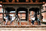 Men observe passers-by from a shady temple spot in Patan's Durbar Square. Nepal, July 2014.
