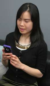 WeCo Certified Test Consultant seated on a sofa using a smartphone.