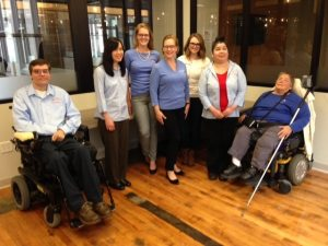 WeCo's staff team posted in their office with a wood floor, two people are in wheel chairs, once is using a cane.