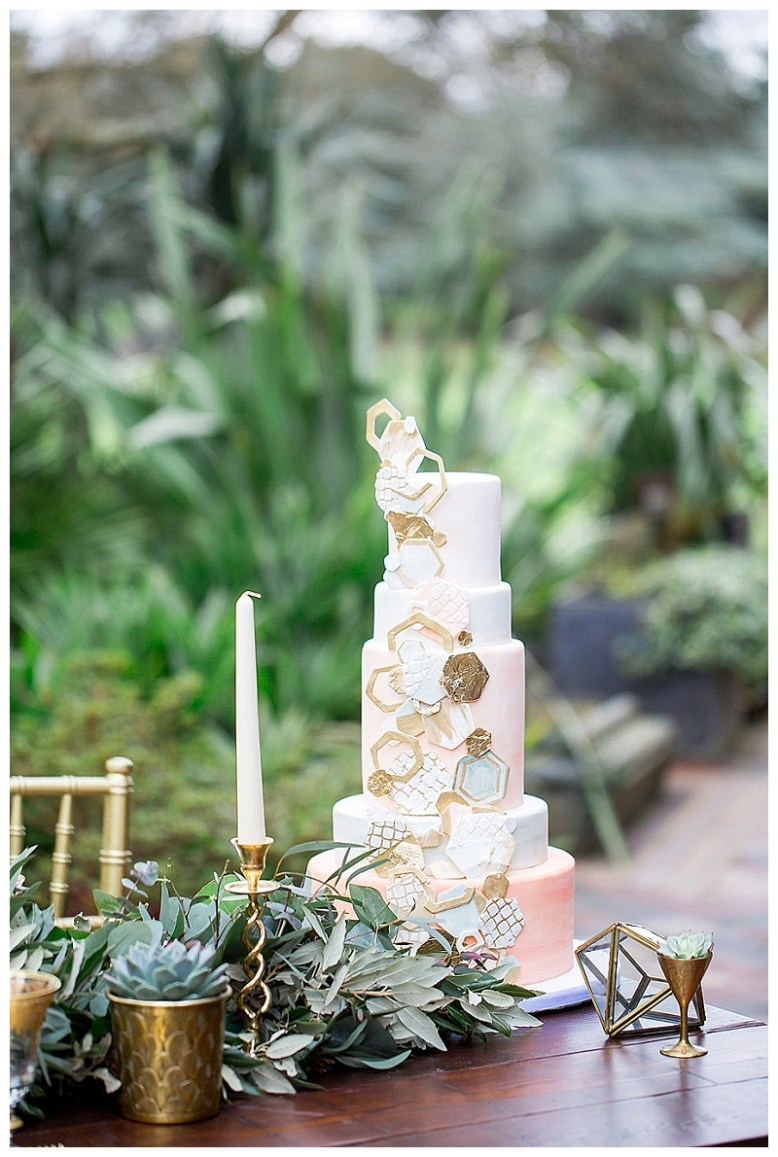 A five tiered ombre cake with cascading hexagons in gold and grey sits on a mahogany table for a modern moroccan styled shoot.