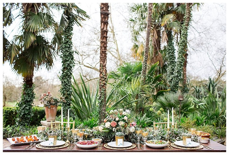 A table is set with gold cutlery, moroccan inspired dishes, trailing foliage and succulents, against a backdrop of palms and ferns.