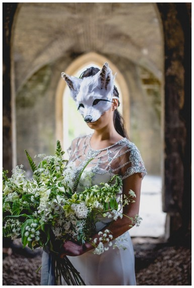 Bride in fox mask with bridal bouquet