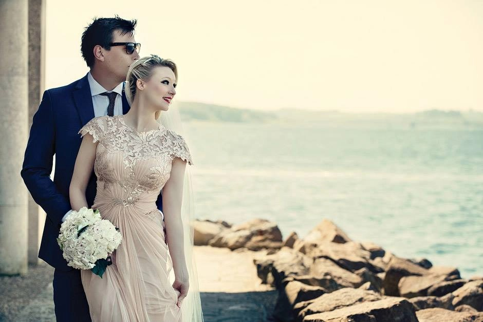 Pretty bride in a Champagne veil looking out to sea with her groom
