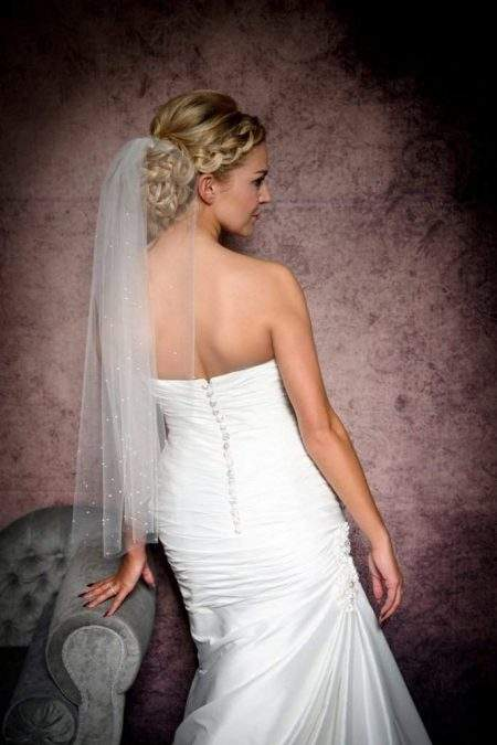 Bride leaning on a chaise wearing a short wedding veil with pearls and diamantes