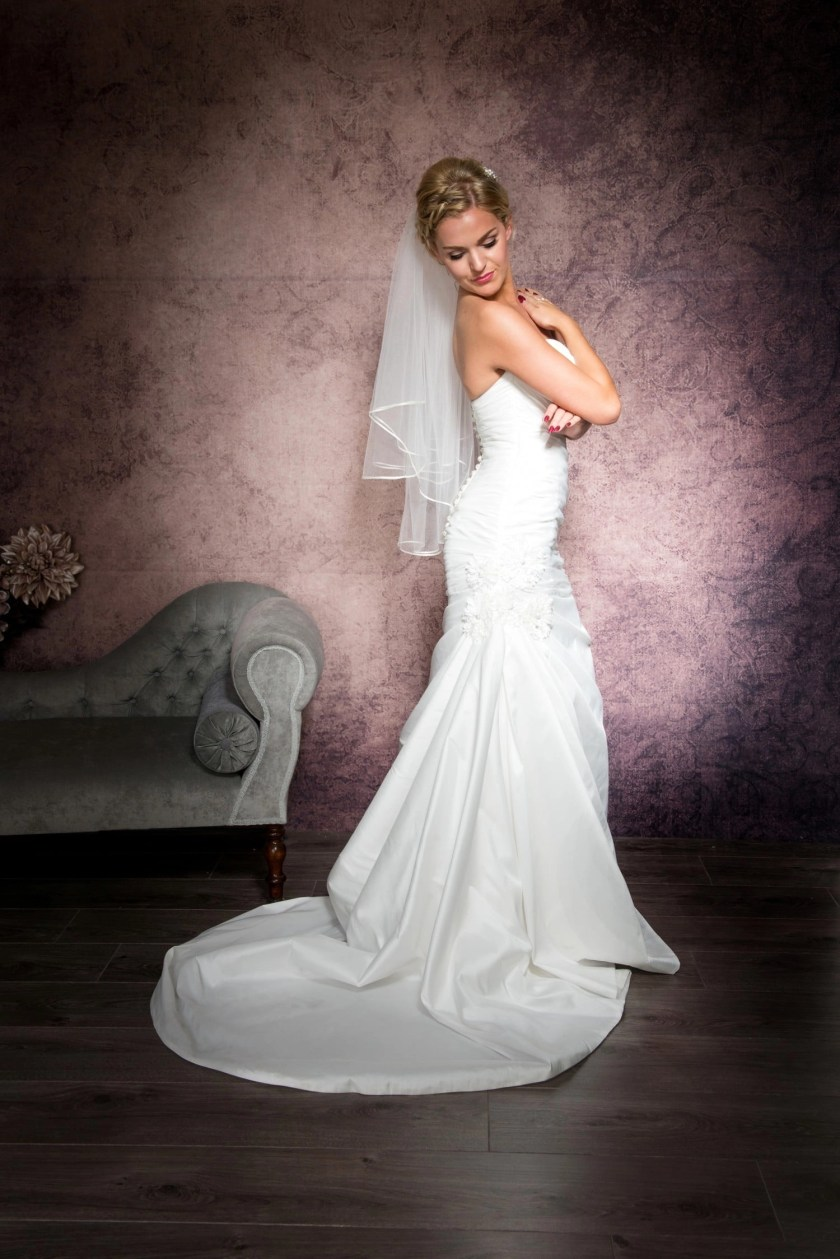 Bride posing in a simple two tier waist length veil