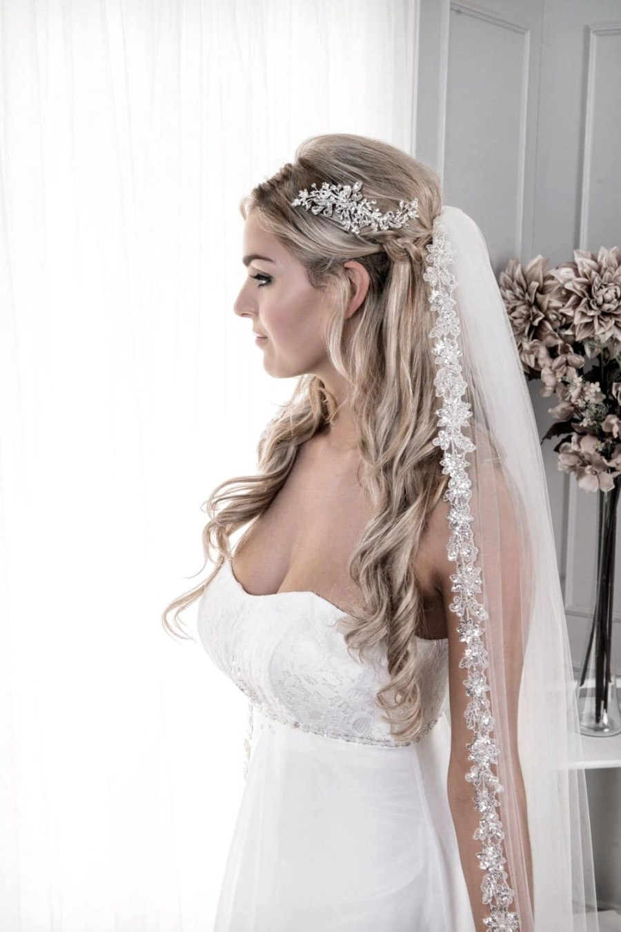 Close up of bride wearing long chapel length single layer veil with a sparkly silver lace edge