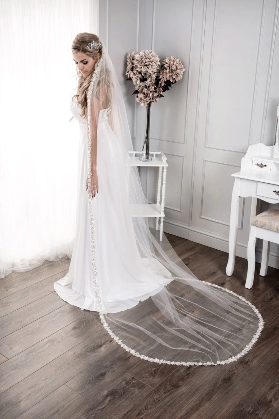 Bride wearing long chapel length single layer veil with a sparkly silver lace edge