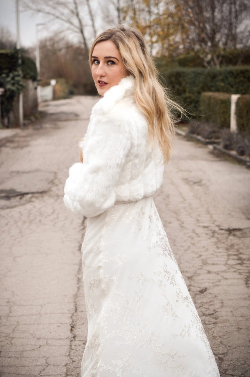 BB20 – bridal jacket with collar and full sleeves in ivory faux fur on blonde bride with hair down on country lane 3