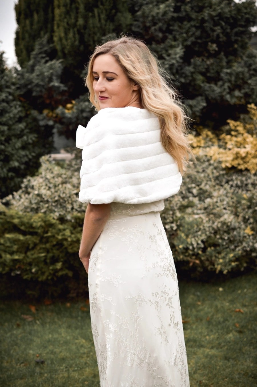 BB22 – faux fur bridal cape wrap shrug with a pretty satin bow on blonde bride with hair down in garden
