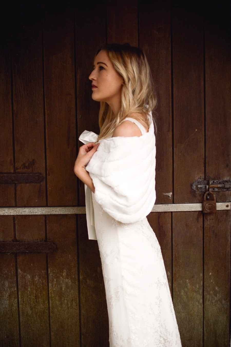 BB22 – faux fur bridal cape wrap shrug with a pretty satin bow on blonde bride with hair down side view stable door