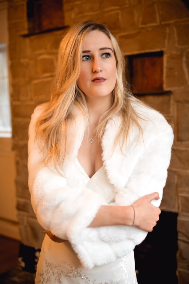 BB42 – faux fur cropped bridal jacket with sleeves on blonde bride with hair down in front of stone fireplace closeup 2