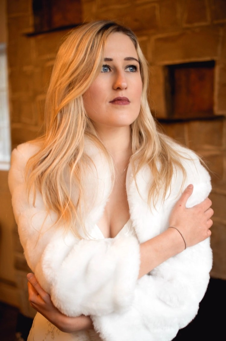 BB42 – faux fur cropped bridal jacket with sleeves on blonde bride with hair down in front of stone fireplace closeup